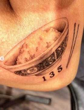 A tattoo of a rice bowl, chops, and the numerals 135 on an arm