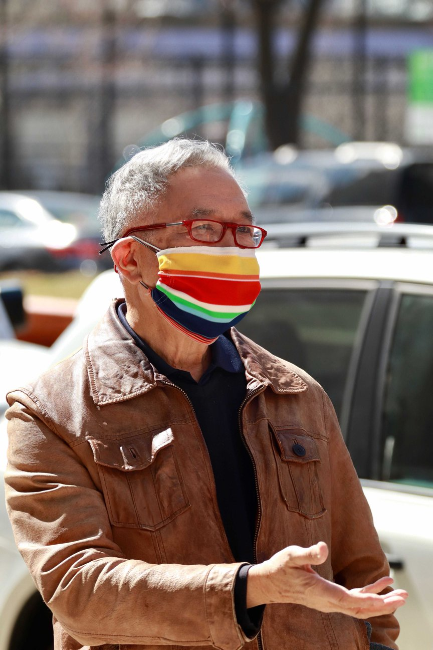 Rocky Chin, wearing glasses and a colorful striped mask, stands on a sidewalk