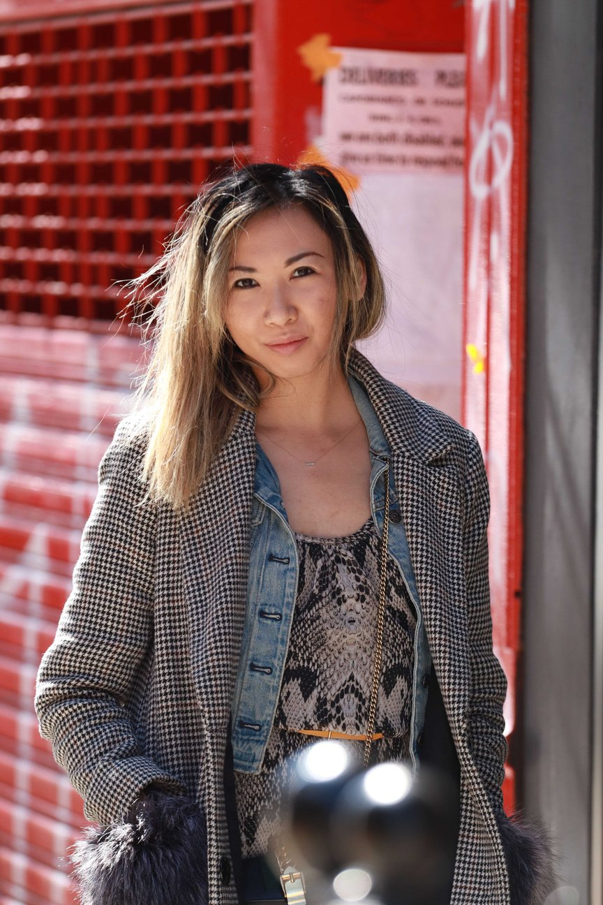 Victoria Lee stands in front of a shuttered storefront