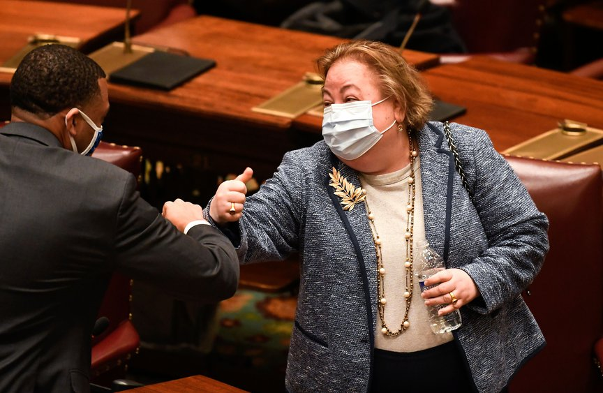 State Senator Liz Krueger, the main sponsor of the MRTA in the Senate, elbow bumps State Senator Jamaal Bailey, of the Bronx, after the bill passed.
