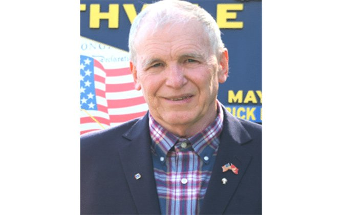 A photo of Durfee in a plaid shirt smiling a the camera