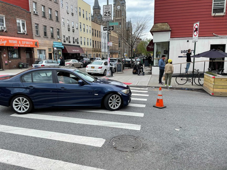 A driver of a BMW stops in front of a single cone at Driggs Avenue and Russell Street.