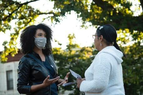 Brooklyn City Council candidate Sandy Nurse, left, talking to a voter outside, both wearing masks to prevent the spread of COVID-19.