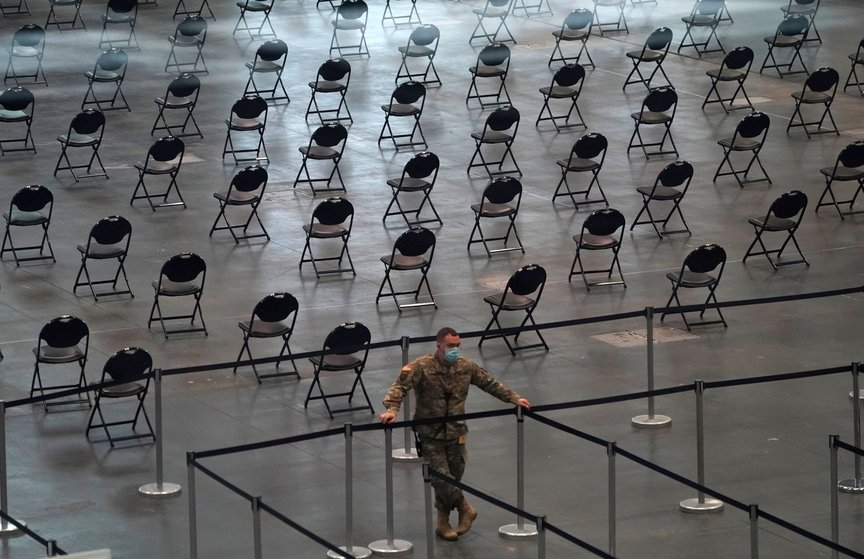 Member of the National Guard looks on as people stand in line at the Jacob K. Javits Convention Center.