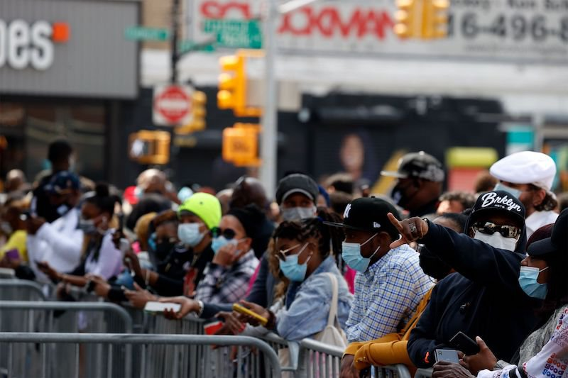 A crowd of masked people stand by metal barricades outside the Barclays Center in Brooklyn, waiting for iconic rapper DMX's memorial.