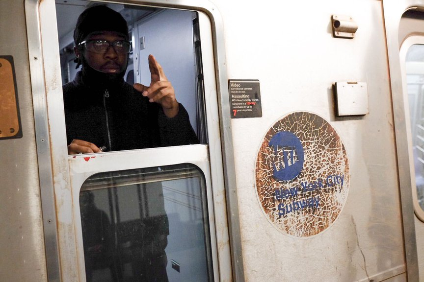 An MTA conductor gestures from his subway compartment