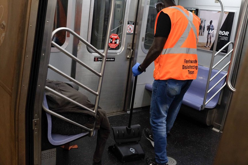 An MTA worker is seen standing next to a person sleeping on a subway bench