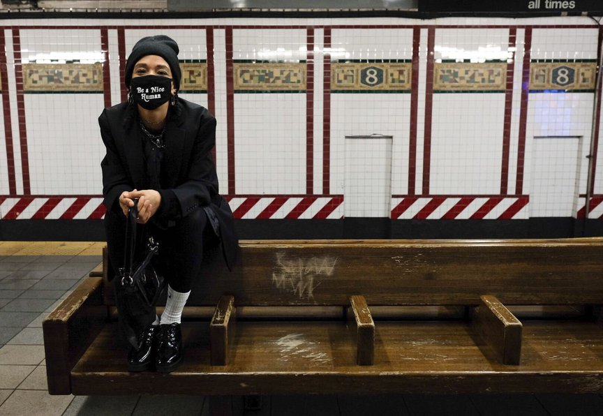 Vanessa Redmond, sitting on the back of a subway bench while in a mask and wearing a beanie on her head