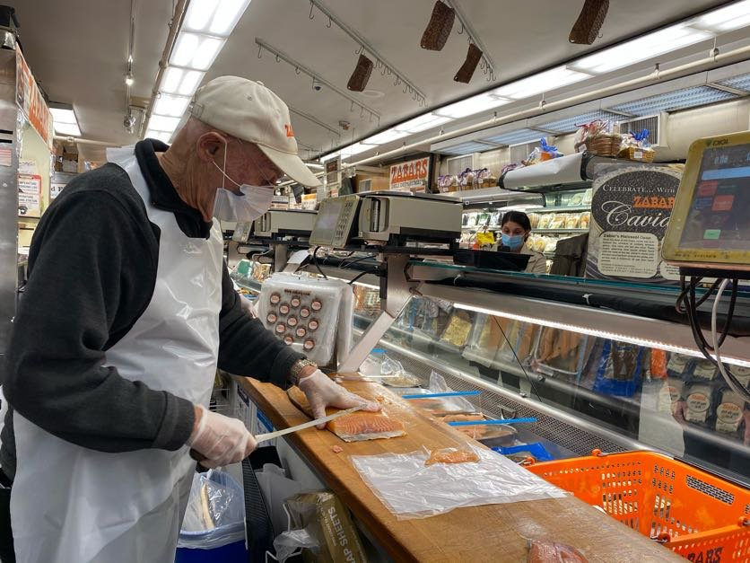 Len Berk slices lox from behind the counter