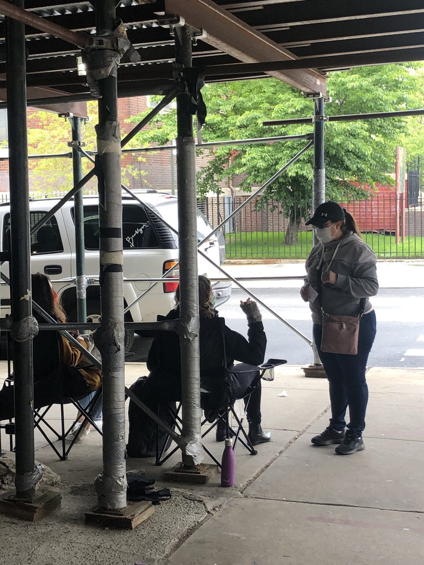 Volunteers sitting outside the shuttered Bushwick Educational Campus inform a woman who approaches that it's been moved to a new location.
