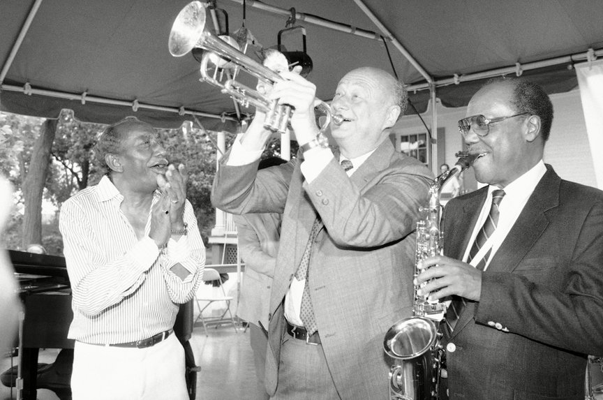 Mayor EdKoch plays the trumpet alongside Joe Newman and Norris Turney. Koch hosted a picnic at Gracie Mansion to kick off the JVC Jazz Festival. 1986.