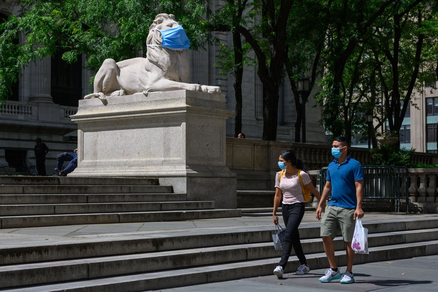 A lion outside the New York Public Library wears a mask while pedestrians also wear masks