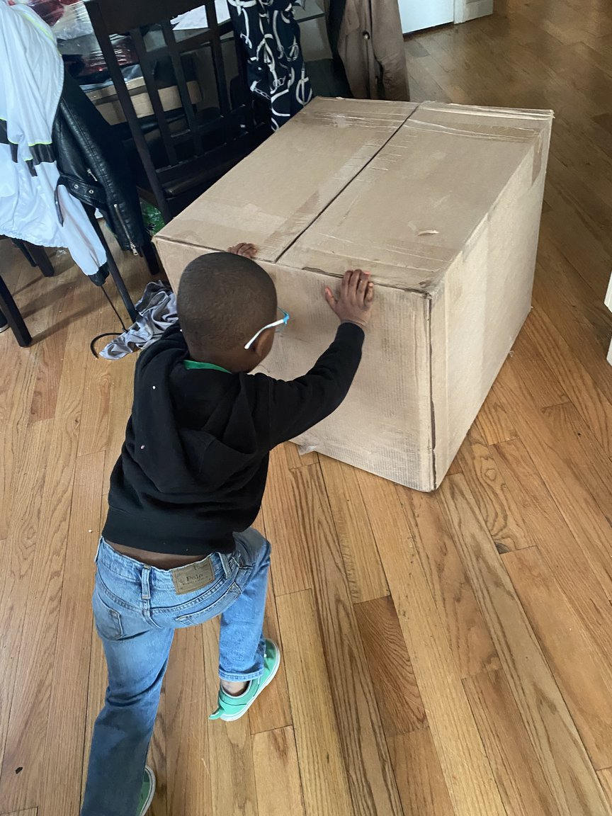 Noah is seen pushing a large cardboard box filled with Spongebob popsicles.