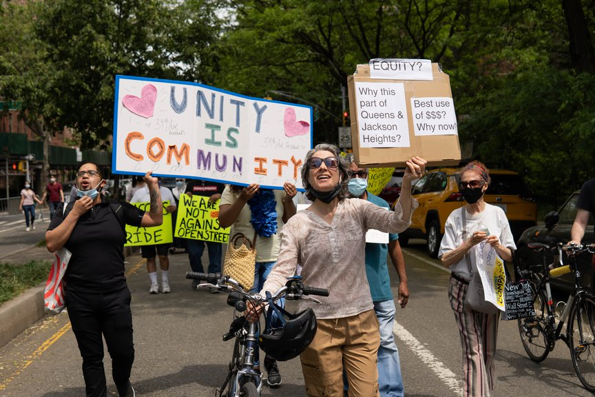 protesters march down 34th Avenue holding signs calling for compromise on Open Streets