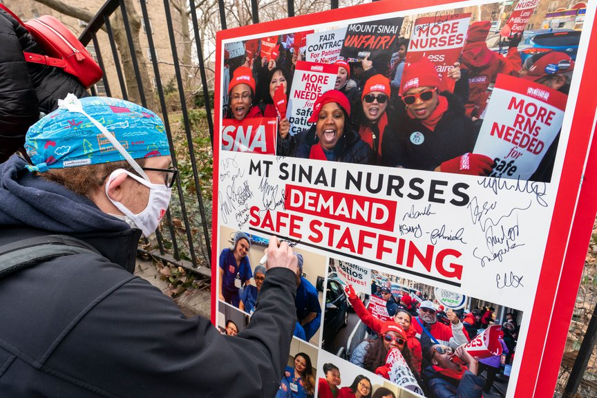 Zach Clapp, a nurse in the pediatric cardiac ICU at Mount Sinai Hospital signs a board demanding safe staffing during a rally held by the New York State Nurses Association, March 16th, 2021.