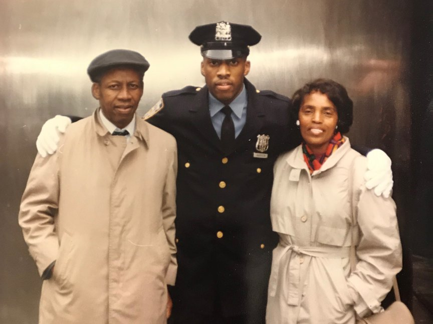 Rodney Harrison stands in his blue NYPD uniform with his arms around his parents, who are wearing tan coats