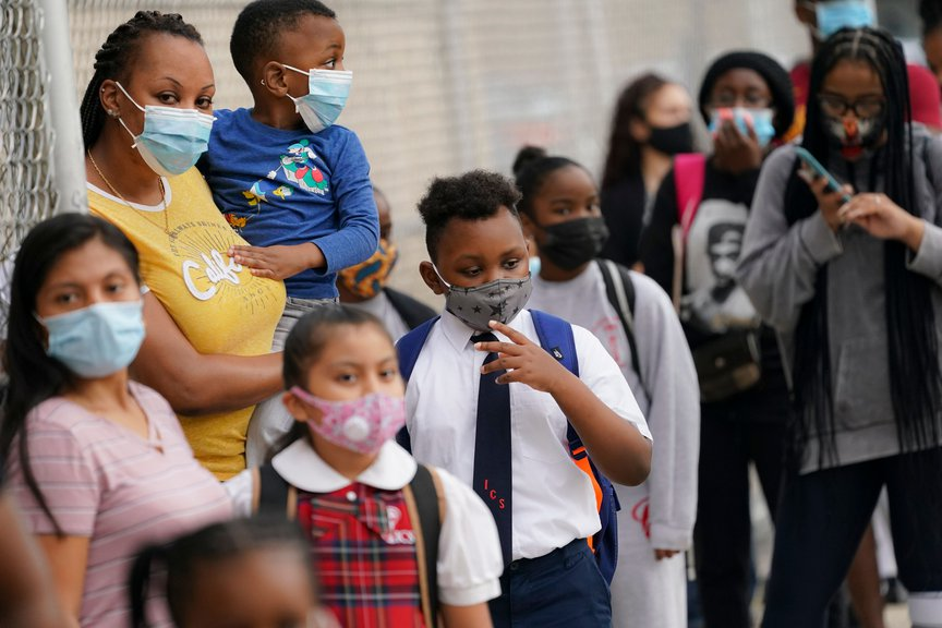 Students wear protective masks as they arrive for classes at the Immaculate Conception School while observing COVID-19 prevention protocols in The Bronx