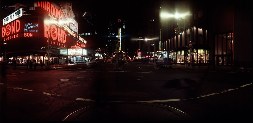 A color photograph of Times Square at night, with the red lights of the Bond's sign visible on the left